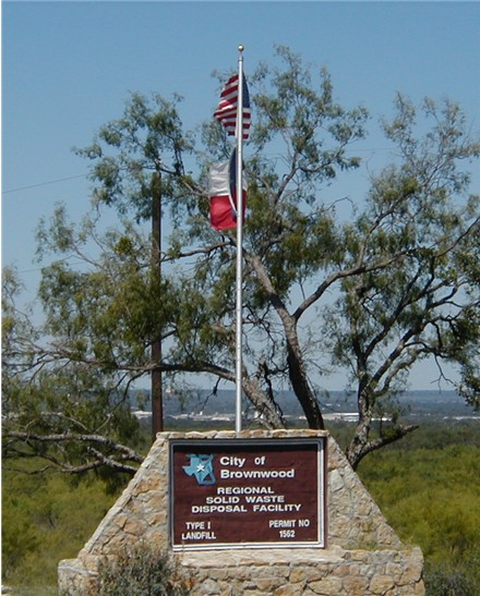The Texas and American flags fly above the Landfill sign that reads - City of Brownwood Regional S