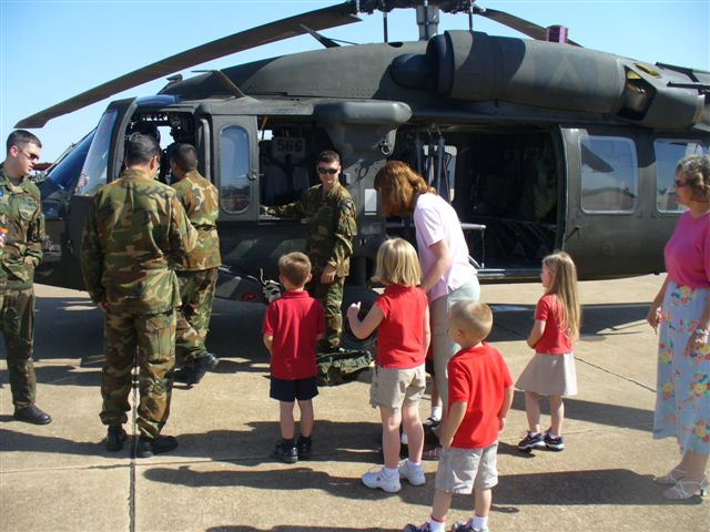 4 men in fatigues give women and children a look inside a military helicopter.