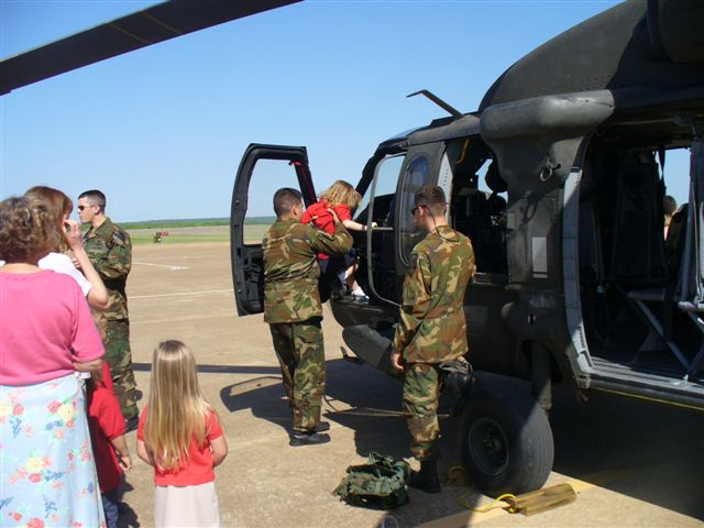 A man in fatigues lifts a young girl into the helicopter cockpit.