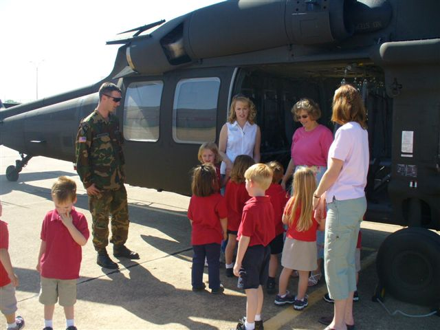 A man in fatigues tells women and children about the military aircraft they are standing in front of.