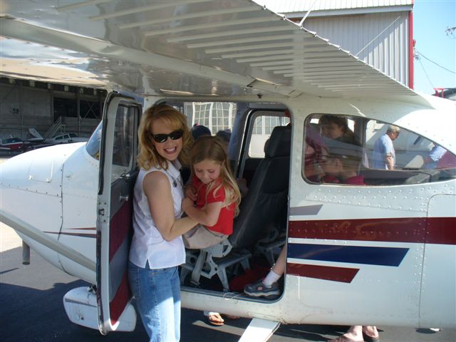 A woman smiles and lifts a young girl out of a small airplane.