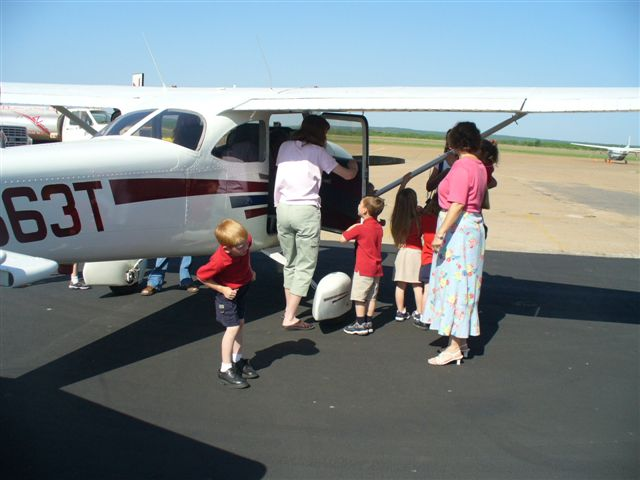 Women and children look inside a small white airplane.