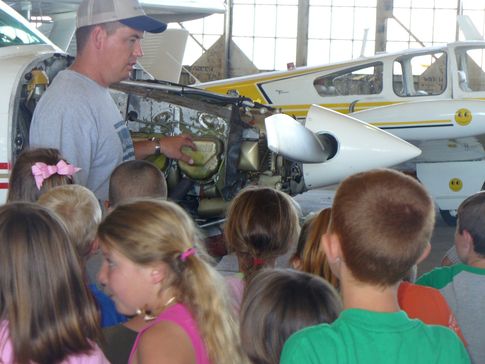 Elementary students gather around an airplane and look at the engine as part of a tour of the airport.