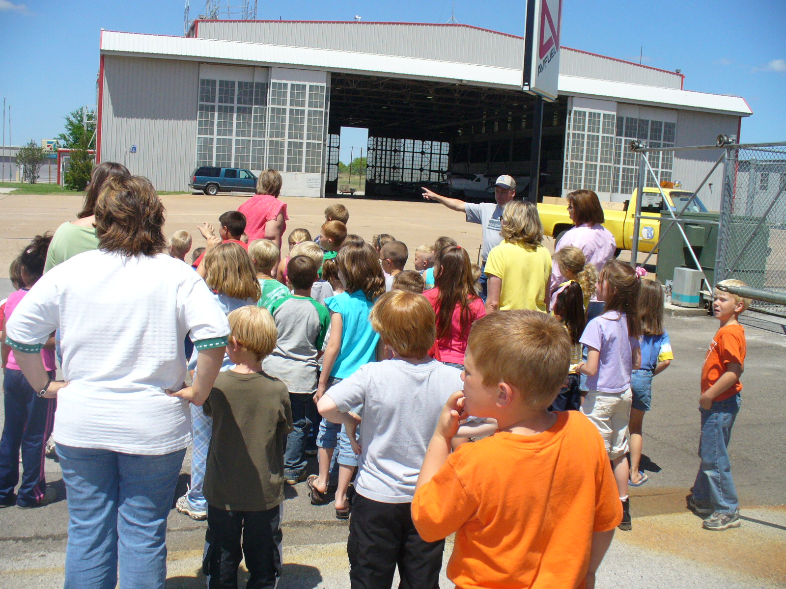 Students and teachers gather outside the airport hangar during a tour of the airport.