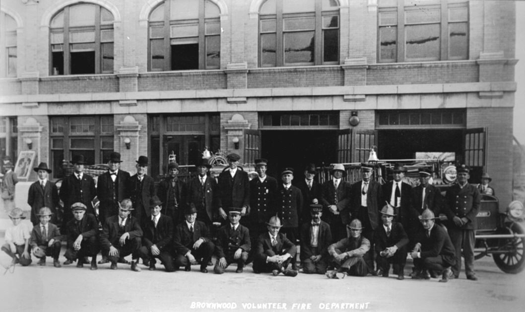 A photo of the Brownwood Fire Department in 1920 with their department trucks and cars.